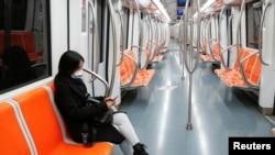 意大利首都羅馬,一名戴著防護口罩的婦女坐在空蕩的地鐵裡,這是意大利政府為減緩新冠病毒蔓延而實施史無前例封鎖的第三天。 (2020年3月12日)