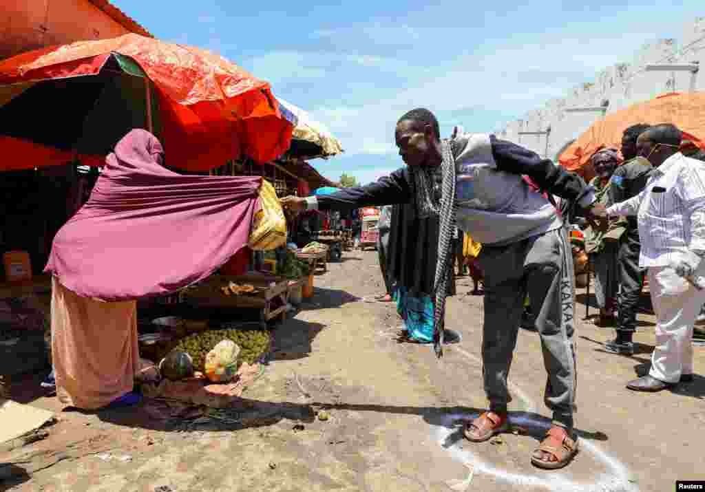 A Somali woman sells fruits to a customer standing at a social distancing signage at the market center in Hamarweyne district in Mogadishu, Somalia.