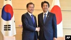 Presiden Korea Selatan Moon Jae-in (kiri) berjabat tangan dengan PM Jepang Shinzo Abe dalam pertemuan di Tokyo, 9 Mei 2018 (foto: dok). Jepang dan Korsel sedang terlibat dalam pertikaian ekonomi.