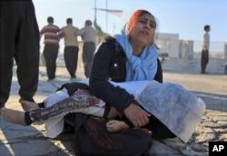 Žena u žalosti dok drži telo svoje ćerke poginule u zemljotresu, u Sarpol-e-Zahabu, zapadni Iran, 13. novembra 2017.