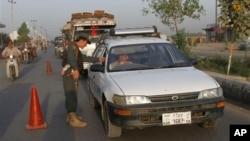 Seorang polisi Afghanistan menghentikan kendaraan di sebuah pos pemeriksaan sementara di Kandahar, selatan Kabul, Afghanistan (16/9). Para petugas keamanan Afghanistan saat ini tengah berada dalam keadaan siaga penuh pasca tertembaknya perempuan pejabat kepolisian senior di wilayah tersebut.