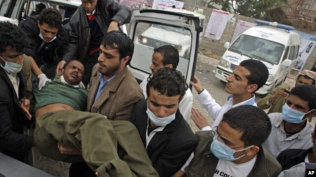 Medics carry an injured anti-government protester into a makeshift clinic in Sana'a, March 13, 2011