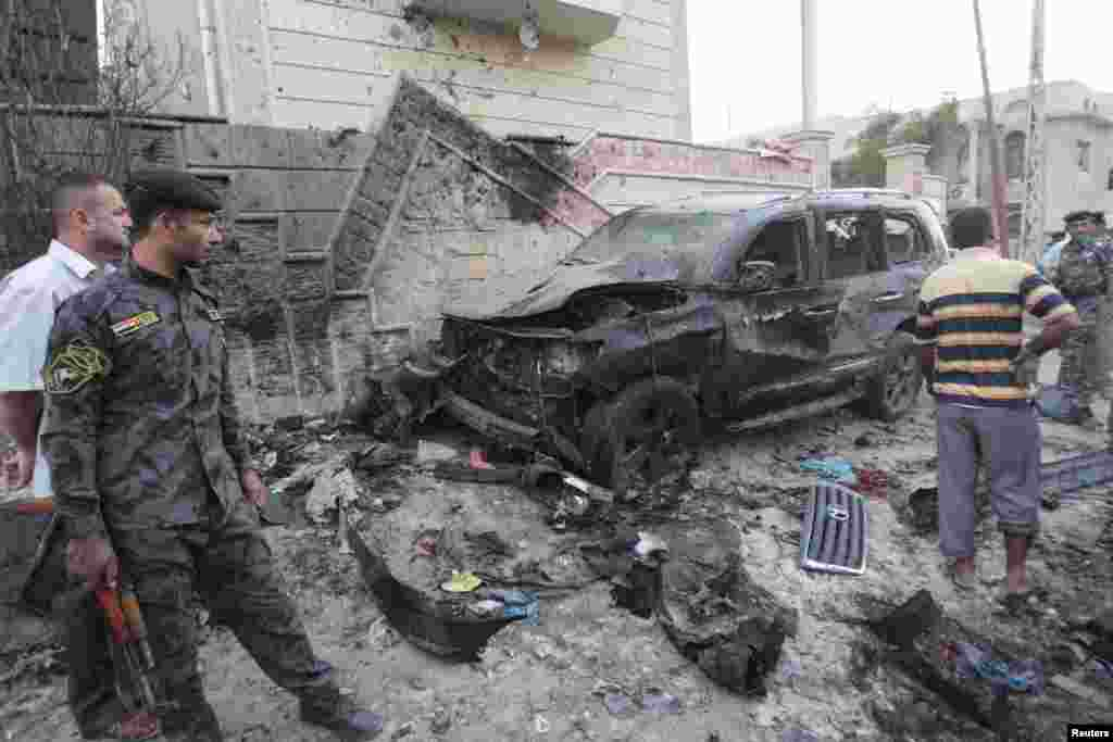 Iraqi security forces inspect the site of bomb attacks in Basra, Iraq, July 14, 2013.