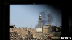 1일 이라크 모술 구시가지 건물 창문에서 보이는 그랜드모스크 첨탑 주변으로 연기가 치솟고 있다.