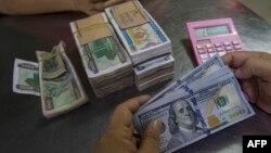 ရန္ကုန္ၿမိဳ႕ရွိ ဘဏ္တခုမွာ ျမန္မာေငြနဲ႔ အေမရိကန္ ေဒၚလာေငြ လဲလွယ္ေနတဲ့ ျမင္ကြင္း။ (ဒီဇင္ဘာ ၁၆၊ ၂၀၂၁)