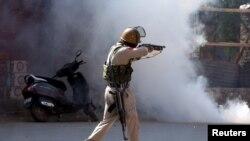 سری نگر میں ایک پولیس اہل کار مظاہرین پر آنسو گیس کا شیل فائر کررہا ہے۔ 27 مئی 2017