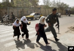 FILE - An Afghan policeman walks with schoolgirls across the road in Herat, west of Kabul, Afghanistan, March 16, 2010.