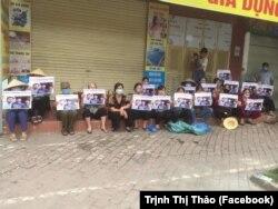 Người dân tập trung bên ngoài với biểu ngữ và hình ảnh của mẹ con bà Cấn Thị Thêu.