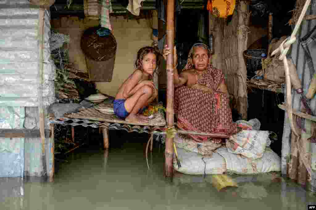 A woman and a young girl sit in their flooded house in Sunamganj, Bangladesh.