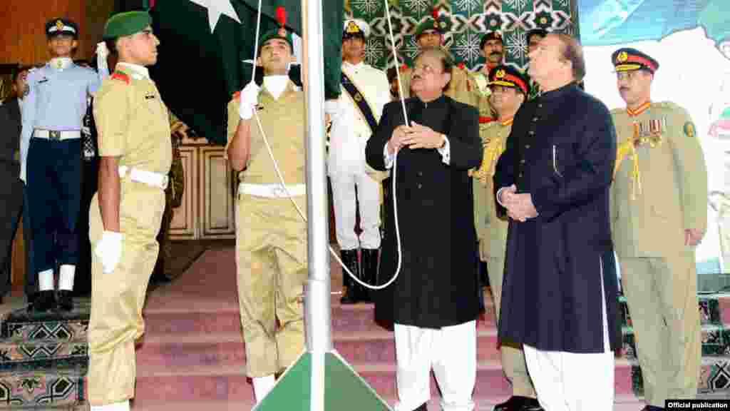 صدر پاکستان ممنون حسین نے قومی پرچم لہرا رہے ہیں۔