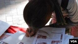 從中國移居香港30多年的徐女士簽署聖誕卡,為六四死難者家屬及在囚異見人士送上祝福(美國之音湯惠芸拍攝)