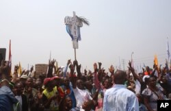 FILE - Supportes of Congo opposition leader Etienne Tshisekedi, rear, hold up a cross that symbolizes no third term for Congo President Joseph Kabila, during a political rally in Kinshasa, Congo, July 31, 2016.