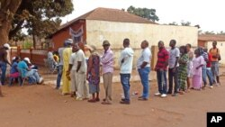 People queue during elections to cast their ballot's at a polling station in Bissau, Guinea-Bissau, May 18, 2014.
