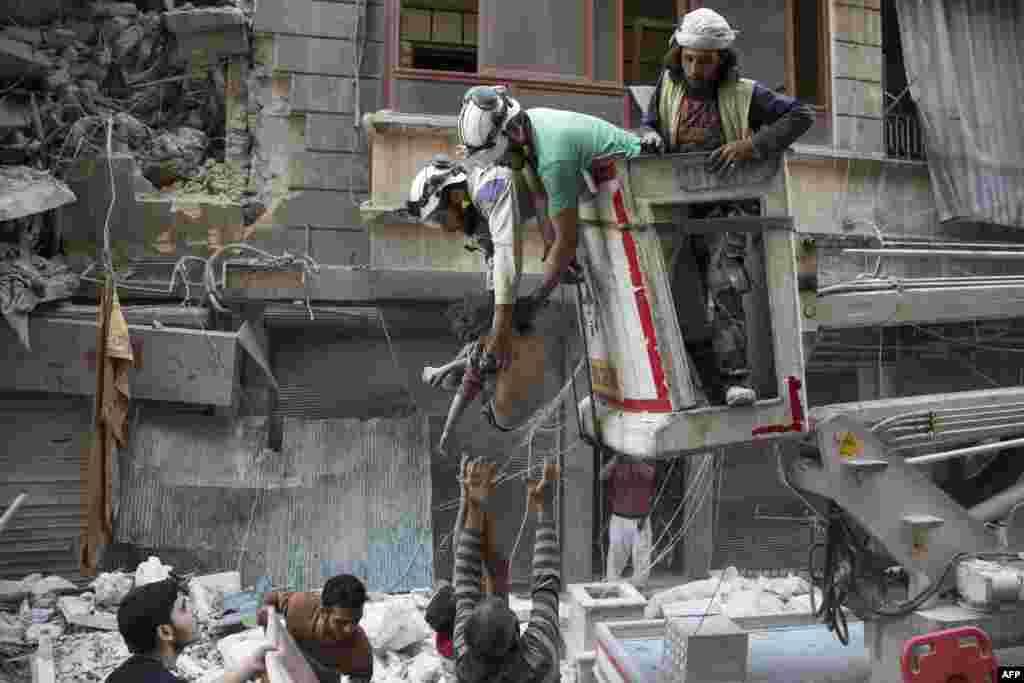 ក្រុមជួយសង្រ្គោះរបស់ស៊ីរីហុចសាកសពក្មេងស្រីម្នាក់ទៅឲ្យជនស៊ីវិលនៅលើដី បន្ទាប់ពីក្មេងស្រីម្នាក់នោះត្រូវបានគេកាយចេញពីកម្ទេចអាការមួយ នៅក្រោយការវាយប្រហារតាមអាកាសរបស់រដ្ឋាភិបាល នៅក្នុងសង្កាត់ Al-Shaar ក្រុង Aleppo។