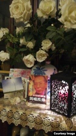 2017年7月19日凌晨,悼念者家中燃烛摆花祭奠刘晓波。(推特图片)