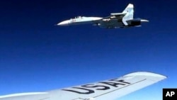 In this image released by the U.S. Air Force, a U.S. RC-135 flying in international airspace over the Baltic Sea is intercepted by a Russian SU-27 jet, June 19, 2017. The Russian military said it scrambled a fighter jet to intercept and escort a U.S. strategic bomber flying over the Baltic along the Russian border.