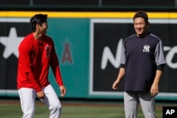 Los Angeles Angels starting pitcher Shohei Ohtani, left, and New York Yankees starting pitcher Masahiro Tanaka, both of Japan, share a light moment on the field before a baseball game Friday, April 27, 2018, in Anaheim, Calif. (AP Photo/Jae C. Hong)