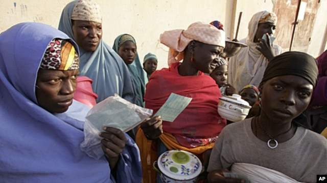 People stand in a food queue at the small town of Tchadoua around 40 kilometers from the town of Maradi, Niger, FILE July 24, 2005.