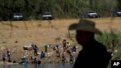 Migrants, many from Haiti, wade across the Rio Grande from Del Rio, Texas, to return to Ciudad Acuna, Sept. 22, 2021, some to avoid possible deportation from the U.S. and others to get supplies.