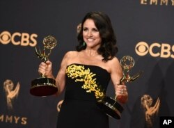 "Julia Louis-Dreyfus poses in the press room with her awards for outstanding lead actress in a comedy series and outstanding comedy series for ""Veep"" at the 69th Primetime Emmy Awards, Sept. 17, 2017, at the Microsoft Theater in Los Angeles."