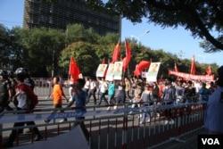 9月18日北京反日示威者手持毛泽东像。韩德强打了对毛泽东持不同政见的老人