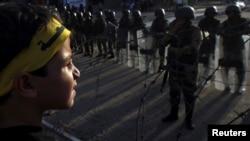 Một cậu bé trong đoàn người biểu tình ủng hộ tổng thống bị lật đổ Mohamed Morsi đứng trước cảnh sát chống bạo động gần Quảng trường al-Rabaa Adawiya tại Cairo, ngày 4/10/2013.