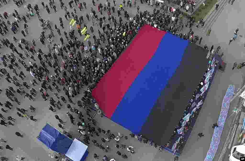 People unfold a giant flag during celebration of the Day of the Flag of Donetsk People's Republic in the town of Donetsk, eastern Ukraine.