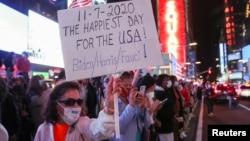 Seorang perempuan mengacungkan poster dan lainnya merayakan pemberitaan media bahwa calon presiden dari Partai Demokrat, Joe Biden, memenangi pemilihan presiden AS 2020, di Times Square, New York City, Sabtu, 7 November 2020. (Foto: Reuters)