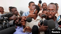 FILE - Somali journalist Abdiaziz Abdinur (R) talks to reporters after the high court freed him in the capital of Mogadishu, March 17, 2013.