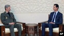 Menteri Pertahanan Iran Amir Hatami (kiri) bertemu Presiden Suriah Bashar al-Assad di Damaskus, Minggu (26/8).