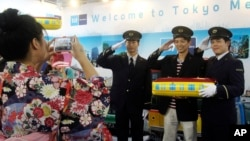 FILE - A Taiwanese visitor poses with uniformed employees of Tokyo Metro Co. for a souvenir photo at the booth of the Tokyo subway company at the Taipei International Travel Fair in Taipei, Taiwan, Nov. 8, 2014. (AP Photo/Chiang Ying-ying)