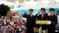 一名台湾游客在东京地铁与穿着制服的工作人员合影。