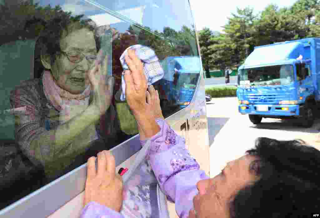 South Koreans (on the bus) bid farewell through the window to their North Korean relatives at the end of a three-day family reunion event at North Korea's Mount Kumgang resort. Elderly North and South Korean family members were allowed to meet for the first time in nearly seven decades.