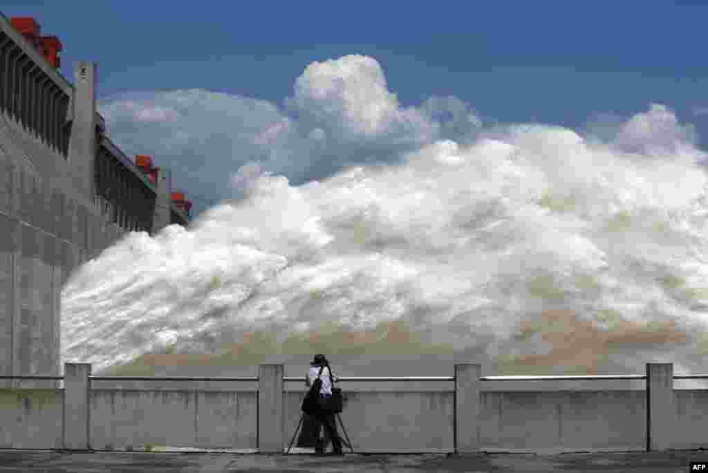 중국 후베이성 양쯔강을 따라 설치된 삼협댐에서 한 남성이 쏟아져 나오는 물을 사진에 담고 있다.최근 폭우로 상류의 물이 불어나면서, 수위 조절을 위해 수문을 열었다.
