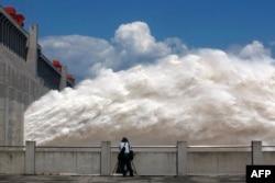 2014年9月3日,三峡大坝开闸放水,一名男子拍摄照片。