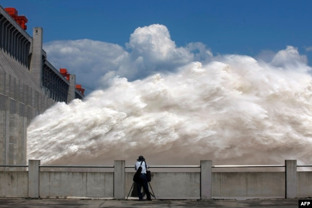 This picture taken on September 3, 2014 shows a man taking pictures of floodwater released from the Three Gorges Dam, a gigantic hydropower project on the Yangtze river, in Yichang, central China's Hubei province, after heavy downpours in the upper reaches of the dam caused the highest flood peak of the year.