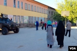 People approach a polling place in Diyarbakir Sunday morning while Turkish troops stand by. (Mutlu Civiroglu/VOA)