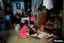Anak-anak mengenakan masker sambil memainkan ponsel di dalam sebuah rumah di kawasan padat penduduk di Jakarta saat pandemi virus corona (Covid-19), 1 April 2020. (Foto: Reuters)