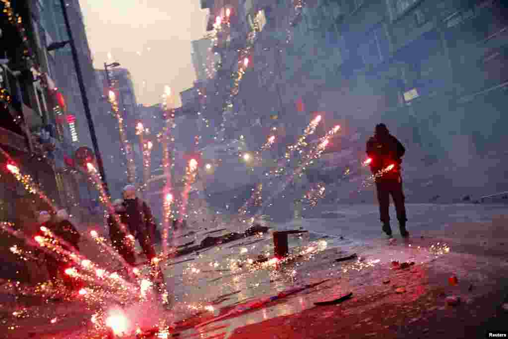 Fireworks thrown by anti-government protesters explode behind riot policemen near central Taksim square in Istanbul. Turkish police fired tear gas and water cannon to push back thousands of demonstrators during a protest triggered by the death of a teenager who was wounded in street clashes last summer.