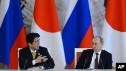 Presiden Rusia Vladimir Putin mendengarkan keterangan PM Jepang Shinzo Abe (kiri) dalam konferensi pers saat berada di Kremlin, Moskow untuk kunjungan kenegaraaan (29/4).