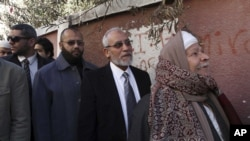 Muslim Brotherhood leader Mohammed Badie, second right, waits in line outside a polling place in Beni Suef, Egypt, to vote on a constitution drafted by Islamist supporters of President Morsi, Dec. 22, 2012.
