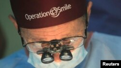 Operation Smile co-founder Bill Magee performs a facial deformity repair surgery for a patient, at the Vietnam Cuba hospital in Hanoi, Nov. 18, 2014.