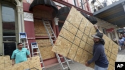 Cesar Reyes, right, carries a sheet of plywood to cut to size as he and Robert Aparicio, left, and Manuel Sepulveda, not pictured, install window coverings at Strand Brass and Christmas on the Strand, 2115 Strand St., in Galveston on Monday, Aug. 24, 2020.