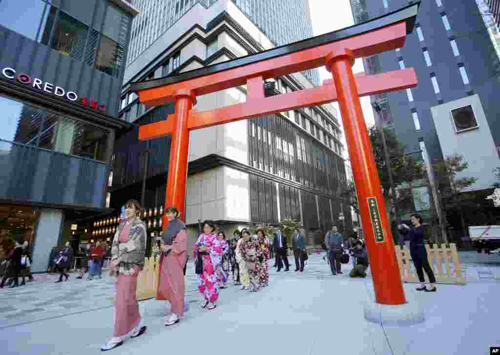 A group of foreign tourists wearing traditional Japanese kimonos walk through a torii gate, the entrance of a shrine, in Nihonbashi shopping and office district in Tokyo.