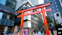 A group of foreign tourists wearing Japanese traditional kimono walk through a torii gate, the entrance of a shrine, in Nihonbashi shopping and office district in Tokyo, Nov. 19, 2014.