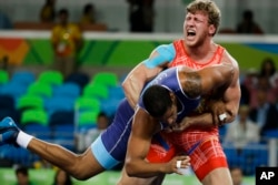 Armenia's Artur Aleksanyan, red, competes against Cuba's Yasmany Daniel Lugo Cabrera for the gold medal during the men's wrestling Greco-Roman 98-kg competition at the 2016 Summer Olympics in Rio de Janeiro, Brazil, Aug. 16, 2016.