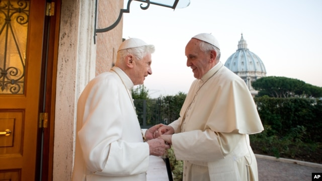 Pope Emeritus Benedict XVI, left, welcomes Pope Francis as they exchange Christmas greetings, at the Vatican, Dec. 23, 2013.
