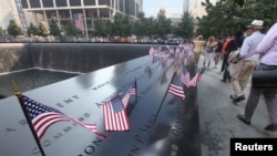 """""""Hàng triệu người đã đến thăm Đài Tưởng niệm biến cố 11 tháng 9, những người đã xướng tên của các nạn nhân, và ngắm thác nước chảy xuống khoảng không sâu bên dưới, thấu hiểu tính nghiêm trọng của biến cố đã xảy ra tại địa điểm này."""" (Ảnh chụp vào ngày đánh dấu 12 năm biến cố 11 tháng 9)"""
