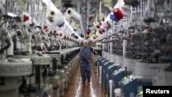 2015年10月22日, 一名工人在阿拉巴马州佩恩堡的 Shankel's 袜子工厂检查机器(路透社)