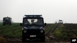 Military vehicles drive to the site of a helicopter crash on the outskirts of Belgrade, Serbia, Saturday, March 14, 2015.